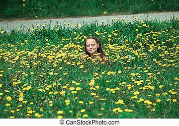 Teenage girl lying in the green grass.