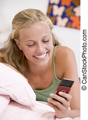 Teenage Girl Lying On Her Bed Using Mobile Phone
