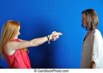 Teenage girl miming gesture of holding a gun