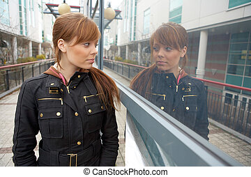 Teenage girl looking at her own reflection in window
