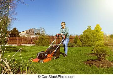 teenage girl mowing grass