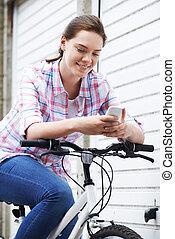 Teenage Girl On Bike Texting On Mobile Phone