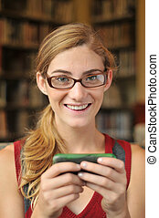 Teenage girl on phone texting in library