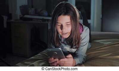 Teenage girl online shopping looks on her smartphone in bed...