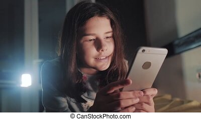 Teenage girl online shopping looks on her smartphone...