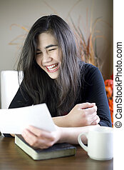 Teenage girl or young woman happily reading note in hand