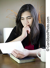 Teenage girl or young woman reading a note, worried expression