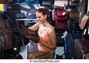 teenage girl picking handbag
