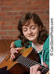 Teenage girl playing the guitar - A teenage girl playing an...