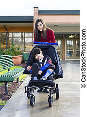 Teenage girl pushing little disabled boy in wheelchair