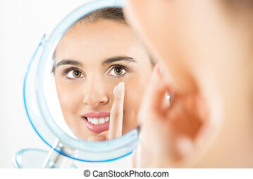 Teenage Girl Putting Cream On Her Face