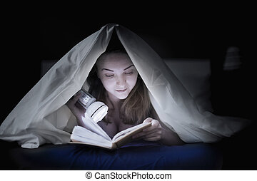 Teenage girl reading a book in bed under the covers