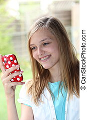 Teenage girl reading a text message on her phone
