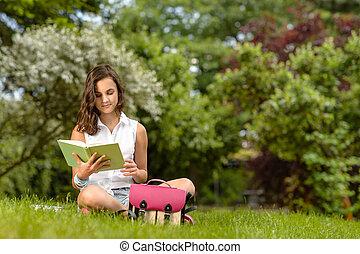 Teenage girl reading book sitting in park