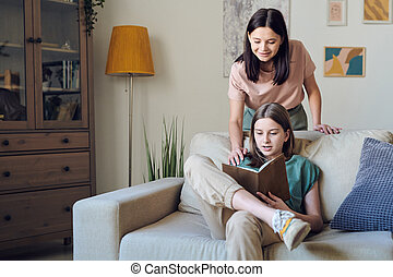 Teenage girl reading book to mother
