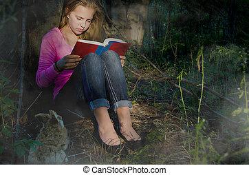 teenage girl reading in foggy woods