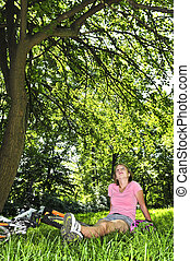 Teenage girl relaxing in a park with her bicycle