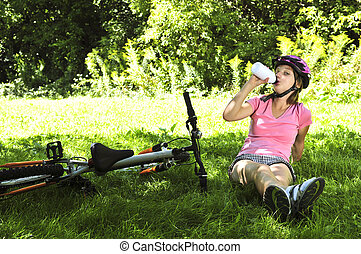 Teenage girl resting in a park with a bicycle drinking water