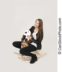 Teenage girl riding a rocking horse