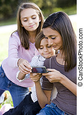 Teenage girl showing mobile phone to younger siblings