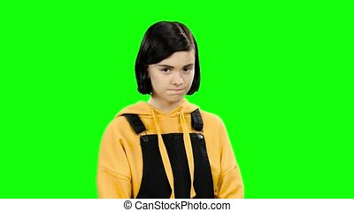 Teenage girl shows a heart shape. Green screen