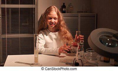 teenage girl sitting at a table in the lab.