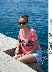 Teenage girl sitting by the sea