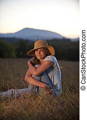Teenage girl sitting in a field