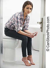 Teenage Girl Sitting In Bathroom With Pregnancy Test