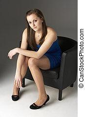 Teenage Girl Sitting In Chair In Studio