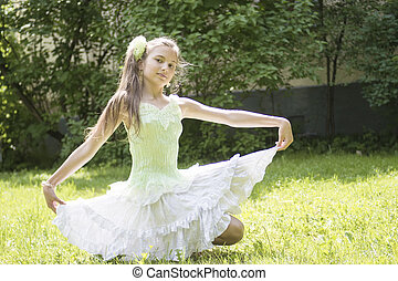 teenage girl sitting in light dress on the grass