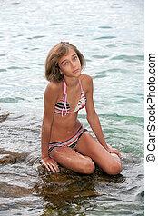Teenage girl sitting on a rock in the sea