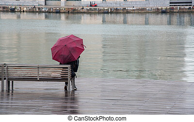 Teenage girl sitting on a wooden bench in the rain