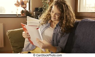 Teenage girl sitting on couch holding notebook, studying -...