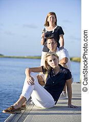Teenage girl sitting on dock by water with parents