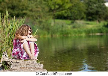 Teenage Girl Sitting On Rock While Looking Away By Lake