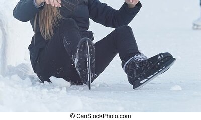 Teenage girl sitting on snow tightening the laces on the...