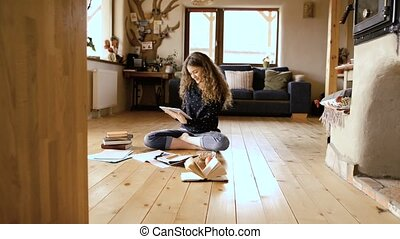 Teenage girl sitting on the floor holding tablet, studying -...