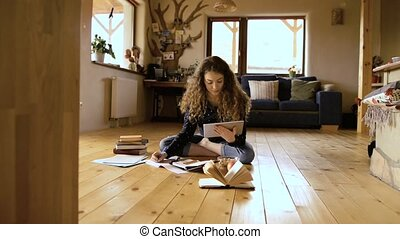 Teenage girl sitting on the floor holding tablet, studying