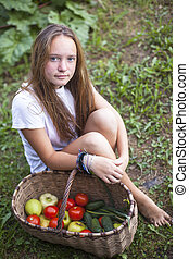 Teenage girl sitting with a basket of vegetables.