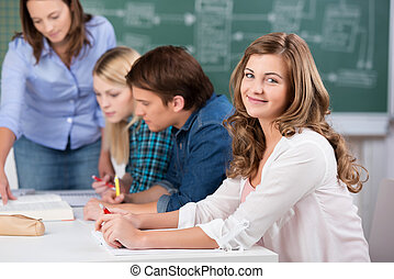 Teenage Girl Smiling With Teacher Assisting Classmates At...
