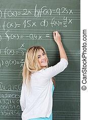 Teenage Girl Solving Maths Sum On Blackboard