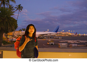 Teenage girl standing at Hawaiian airport making shaka sign