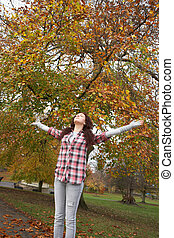 Teenage Girl Standing In Autumn Park With Arms Outstretched