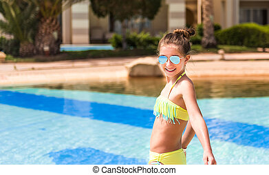 Teenage girl standing in front of pool