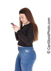 Teenage girl standing in profile looking at her smartphone