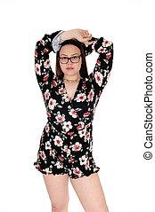 Teenage girl standing with hands on head