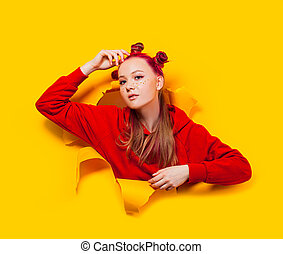 Teenage girl sticking out of torn hole in a yellow paper wall