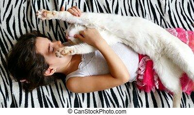 Teenage girl stroking cat lying on the bed love - Teenage...