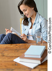 Teenage girl student reading book at home